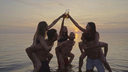 The six friends clink bottles on the water on a sunset background. slow motion Live Action