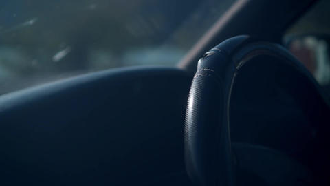 Closeup of a steering wheel driving a car. A cover with a textured relief is Live Action