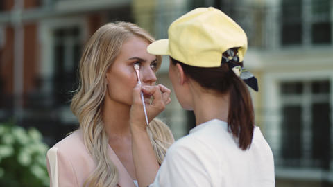 Closeup make up artist doing make up. Actress preparing for filming outdoor Live Action