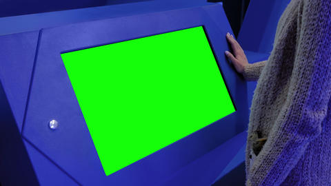 Green screen concept - woman looking at blank interactive green display kiosk Live Action