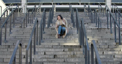 Young attractive Caucasian woman stopping on stairs because of ankle pain. Young Live Action
