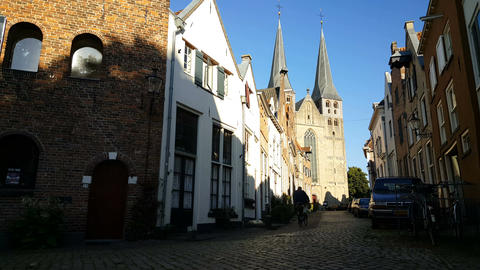 Man riding a bicycle in an alley in historic Deventer Footage