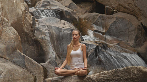 Blond Girl Sits in Yoga Pose Lotus on Stone by Waterfall Footage