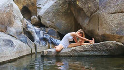Blond Girl in Pose Half-Lotus Stretches along Leg on Stone Footage