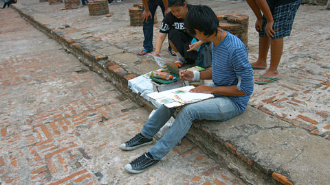 AYUTTHAYA. THAILAND - CIRCA FEB 2015: Local Artists Sits on a Step and Paints at Footage