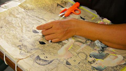 BANG PA-IN. THAILAND - CIRCA NOV 2013: Local artisan stitching parts of an image Live Action
