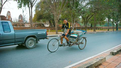 AYUTHAYA. THAILAND - CIRCA FEB 2015: A pedicab driver smiles and waves at the ca Live影片