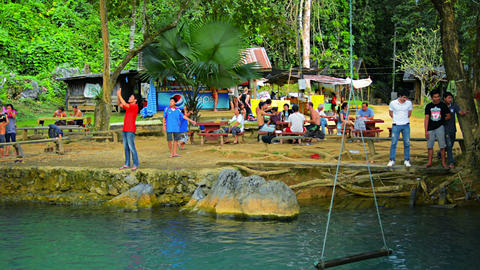 VANG VIENG. LAOS - CIRCA DEC 2013: Tourists leaping playfully into the cool. ref Footage