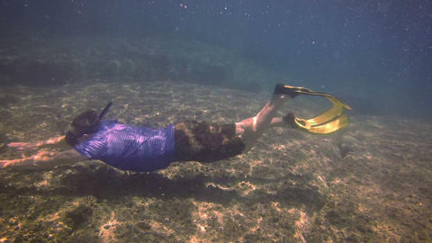 Underwater Shot of a Snorkeler Swimming Along a Rocky Sea Floor in Thailand Footage