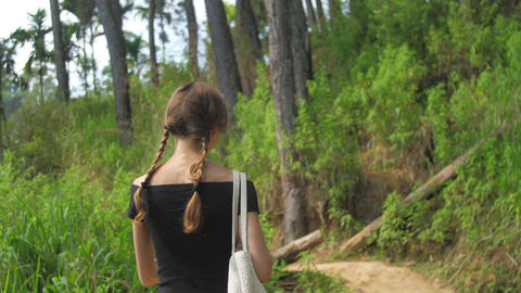 slim girl walks along highland path surrounded by trees Live Action
