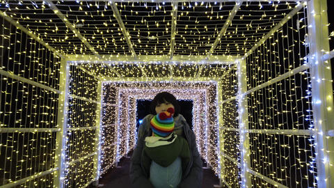 Parent and Little boy walk in illuminated tunnel Live Action