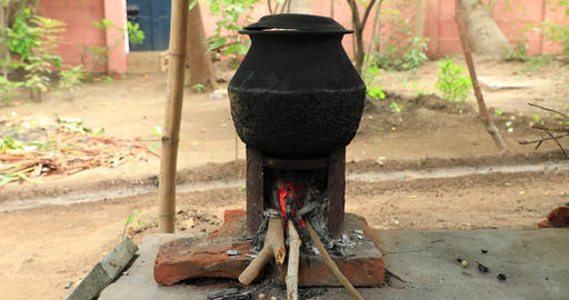 Water heating using firewood in a rural village early in the winter season Live Action