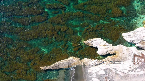 Overhead view of rocky sea shore with crystal clear water Live Action