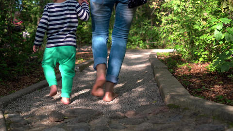Mom with children walking through rough path with little stones Live Action