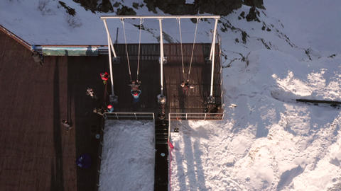 Aerial view people swinging on swing on cliff edge on winter mountain landscape. Tourist people Live Action