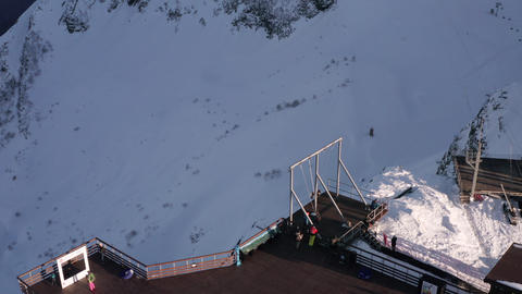 Tourists swinging on swing on cliff edge on winter mountain landscape. Aerial landscape from drone Live Action