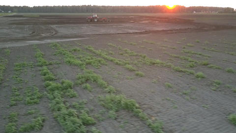 wide field and cultivator plowing soil at dusk bird eye view Live Action