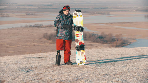 14-12-19 RUSSIA, KAZAN: Snowboarding - A man with prosthetic leg standing on the Live Action