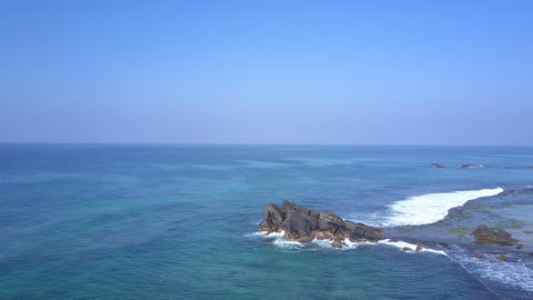lady meditates on large rocky cliff at endless blue ocean Live Action