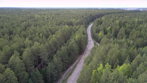 sport utility vehicle drives from village on horizon aerial Live Action
