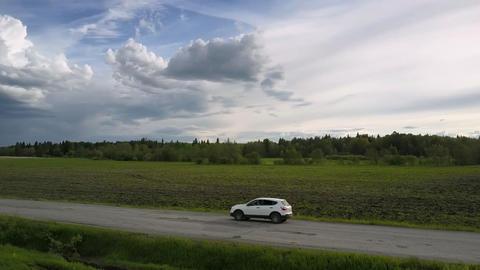 vehicle drives along old asphalt road under pictorial clouds Live Action