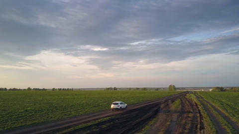 car moves along narrow road past accurate green fields Live Action