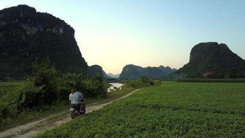 people travel among field at river against mountains aerial Live Action
