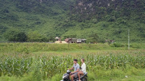 people travel on scooter at rural site near mountain aerial Live Action