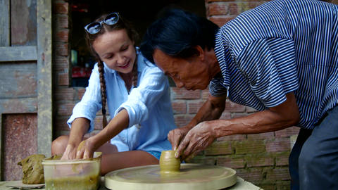 woman in blue blouse learns to make clay pot on wheel Live Action