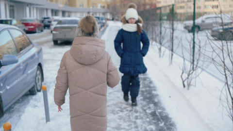 Young girl in winter hat with pompon and down jacket walking in winter city back Live Action