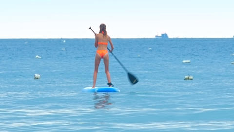 back lady paddles board in ocean against boat on horizon Live Action