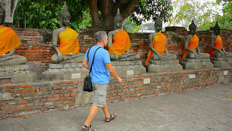 Tourist Visits Ancient Buddha Statues at Wat Yai Chai Mongkol in Thailand Footage