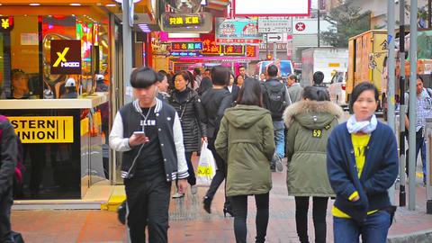 Heavy morning pedestrian traffic on a sidewalk along a busy city street in a dow Footage