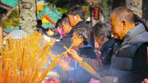 Buddhists offering incense and prayers on an alter at Wong Tai Sin Temple in Hon Footage