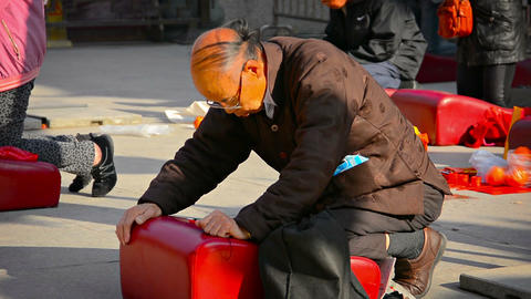 Elderly buddhist worshipper bowing and praying on a cushion before an alter at W Footage