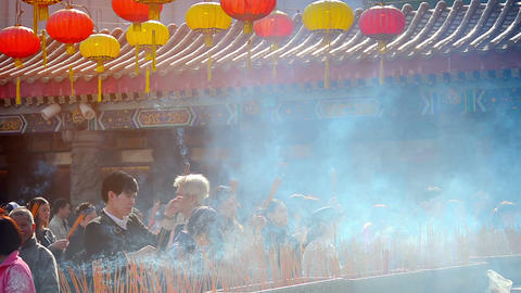 Buddhist worshippers offering incense to the Buddha at Wong Tai Sin Temple in Ho Footage