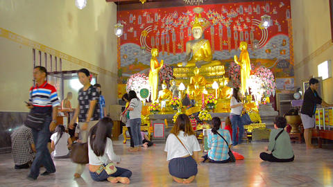 Buddhist worshippers kneel and pray before a gilded image of the Buddha at a tem Footage