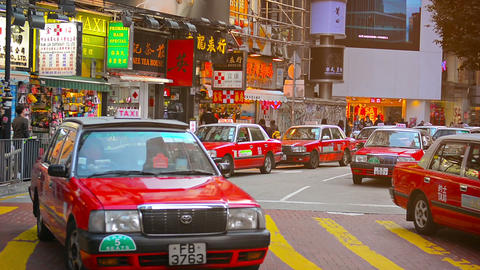 Long line of red and white taxis waits for passengers at a busy shopping area in Footage