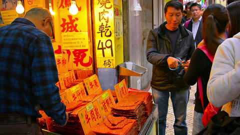 Vendor cuts off samples of a product for passersby in this crowded commercial di Footage