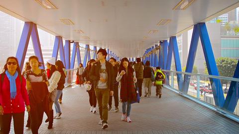 People crossing a pedestrian bridge to Hong Kong Piers Footage