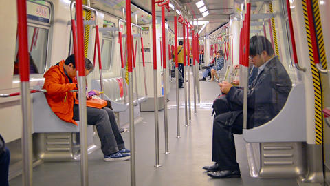 Passengers using their smart phones while commuting on a subway train in downtow Footage