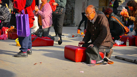 Buddhist worshippers kneel on cushions and pray before an altar at Wong Tai Sin Footage
