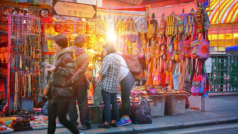 Customers browsing a vendor's wares at a stall at the Jade Market on Kansu Stree Footage