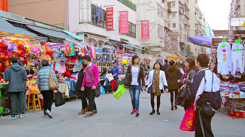 Shoppers strolling through a busy. outdoor. downtown market. in Hong Kong. brows Footage