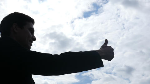 Silhouette of Businessman Showing Thumbs Up Sign for Success, Outdoor Footage