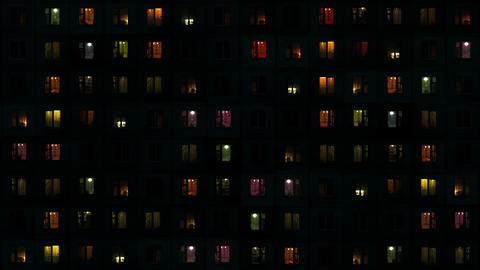Light in the windows of high-density apartment block at night Footage