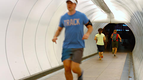 Joggers running both directions through a special tunnel designed for pedestrian Footage