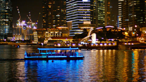 Tour boat. lit up in blue. cruises through Marina Bay. with the dramatically lig Footage