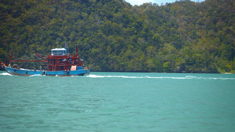 Fishing Boat Passing a Forested Tropical Island in Timelapse Footage