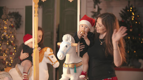 Christmas concept - Two babies sitting on carousel horses indoors and playing Live Action